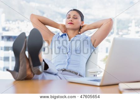 Attractive businesswoman relaxing in her office with her foot on the desk
