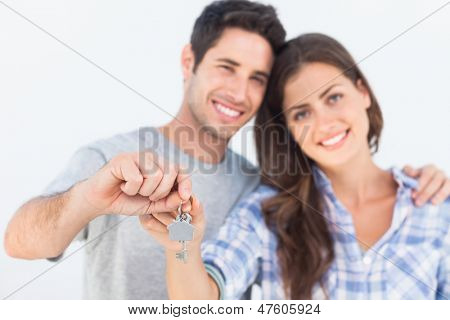 Cheerful man and wife holding a key with a house keychain