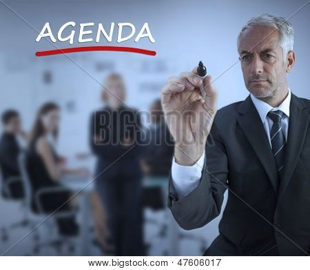 Sophisticated businessman underlining in red the word agenda during a meeting