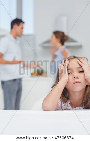 Girl annoyed while listening to parents quarreling in the kitchen