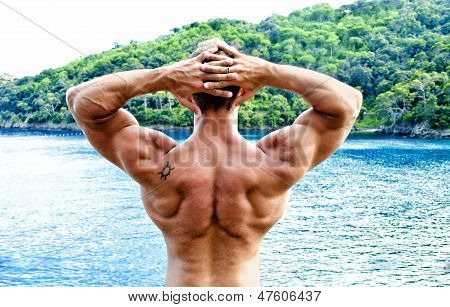 Muscular Bodybuilder Facing The Sea With Hands Behind His Head