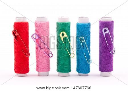 spool of threads and safety pins
