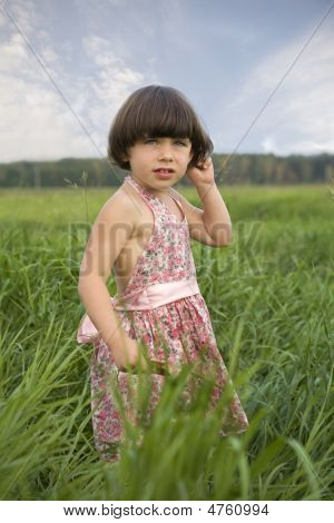 Little Girl Standing In Grass Of Meadow. Summer Time