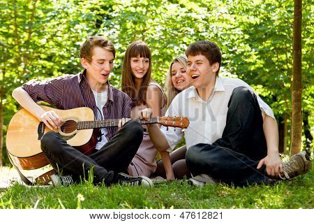 Four Friends Singing By Guitar
