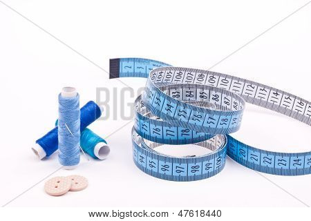 spool of threads ,needle and measuring tape