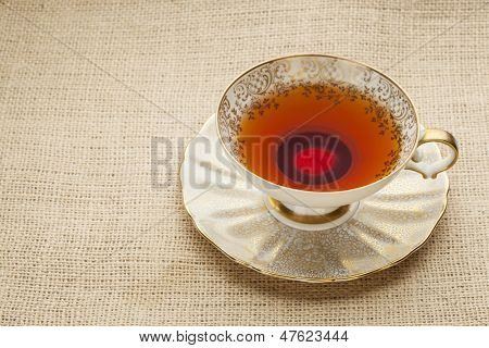 afternoon tea - antique cup of black tea on canvas  (burlap)background