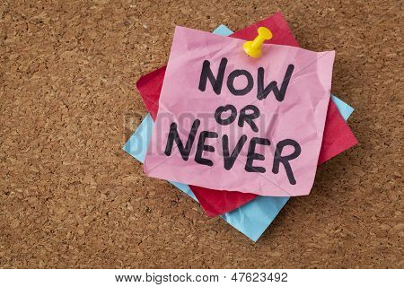 now or never  - motivational reminder on a green sticky note
