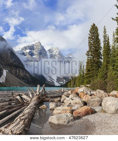 Moraine Lake, glacially-fed lake, Banff National Park, Alberta, Canada, in the Valley of the Ten Peaks. Surrounded by snow covered peaks of the Rocky Mountains with logs floating in the foreground.