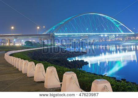 City night scene with illuminated bridge over river in Taipei, Taiwan, Asia. The bridge was named MacArthur Bridge No. 2.