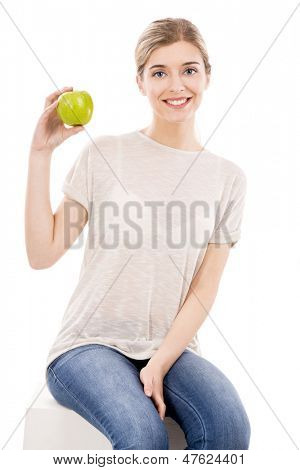 Beautiful blonde girl sitting and holding a green apple, over a white background