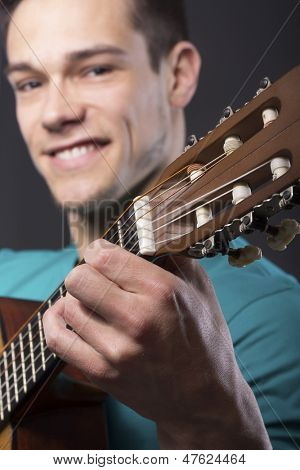 Close-up Of Happy Young Man With Guitar Over Gray Background