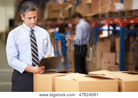 Manager In Warehouse Checking Boxes