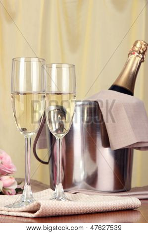 Champagne and glasses on round table on cloth background