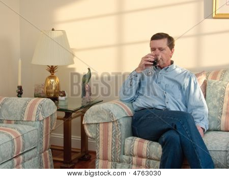 Middle-aged Man Relaxes On Sofa In Modern Living Room