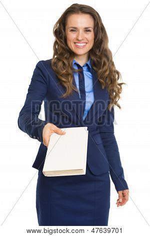 Sonriente mujer de negocios que libro