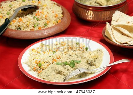Homemade, indian-style dinner of fish in green curry sauce served with three-coloured vegetable pilau rice and a plate of chappatis.