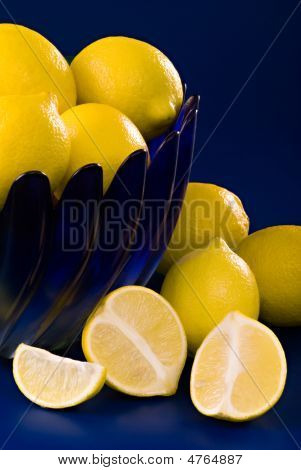 Lemons In Blue Bowl On Blue Background