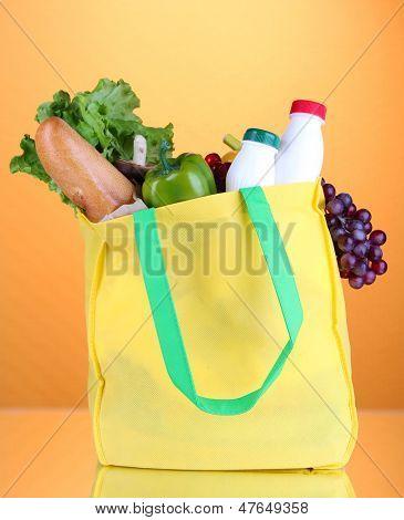 Eco bag with shopping on orange background