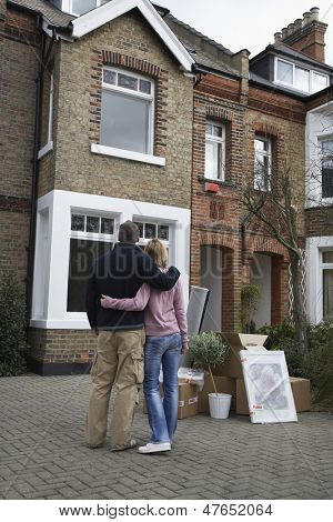 Rear view of a couple looking at house with possessions outside