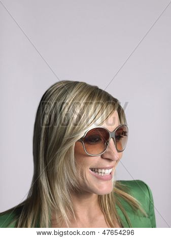 Closeup of a smiling blonde young woman wearing sunglasses against gray background