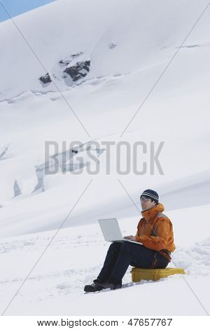 Side view of a male hiker using laptop on snowy mountain landscape