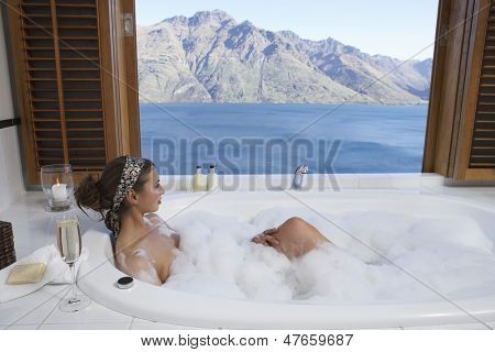 Side view of a young woman taking bubble bath with mountain lake outside window
