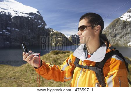 Side view of a male hiker using compass in by the mountain lake