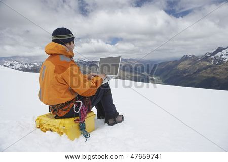 View of a male hiker using laptop on snowy mountain landscape