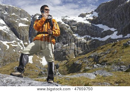 Full length low angle view of a male hiker using cellphone with walking stick in mountains