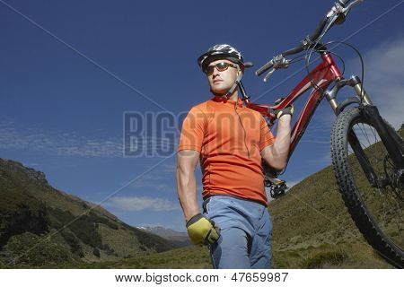 Male cyclist carrying bike against hills and blue sky