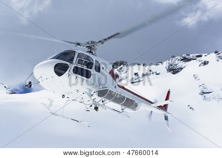Low angle view of a helicopter flying over snowy mountain peaks