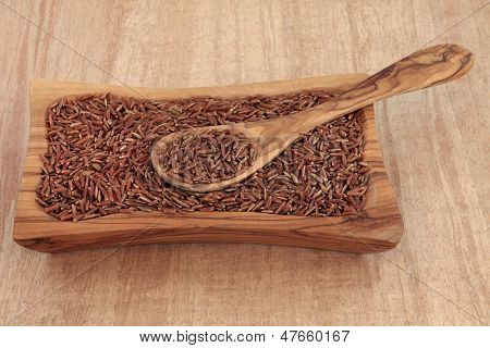 Bhutanese red rice in an olive wood bowl with spoon over papyrus background.