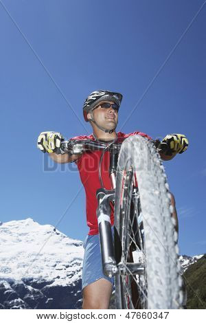 Low angle view of a male cyclist riding against mountains and clear blue sky