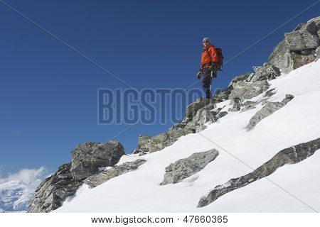 Low angle view of a male mountain climber descending snow and boulder slope