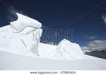 Side view of two hikers walking past ice formations at a distance in snowy mountain