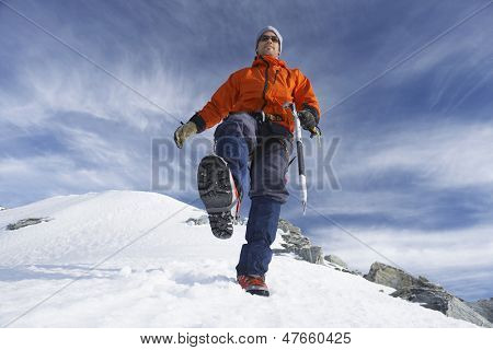 Low angle view of a male mountain climber hiking on snowy slope