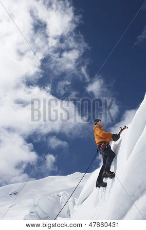 Low angle view of a male mountain climber going up snowy slope with axes against clouds