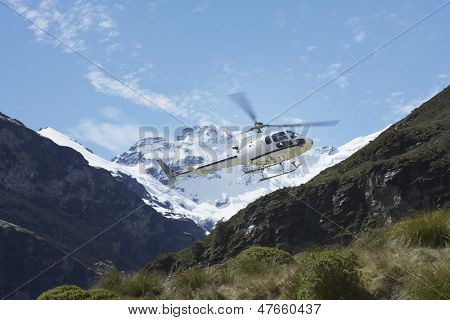 Low angle view of helicopter over mountains
