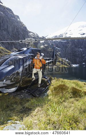 Male hiker climbing out of helicopter on mountain top