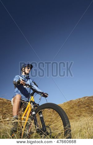 Low angle view of a young woman riding bicycle in field against clear blue sky