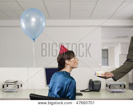 Side view of a woman in party hat blowing birthday candle on cake in office