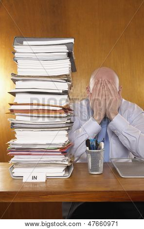 Businessman covering face with hands next to stack of paperwork at folders