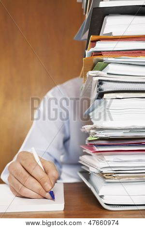 Cropped shot of a man writing document behind a stack of folders at desk