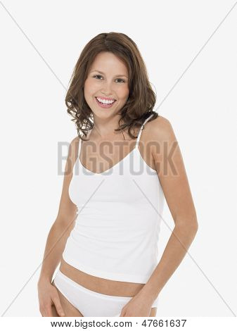 Portrait of a young smiling woman in camisole and knickers against white background