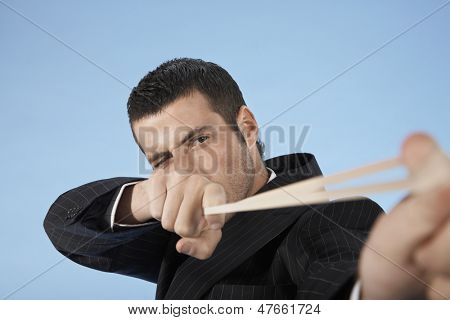 Closeup of a young businessman aiming rubber band on blue background