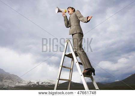 Low angle view of businesswoman on ladder shouting through megaphone in mountain field