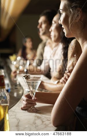 Side view of young multiethnic group at the bar with cocktail glasses