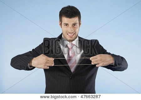 Portrait of a young businessman stretching rubber band on blue background