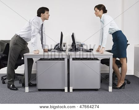 Side view of a male and female rival business colleagues in office