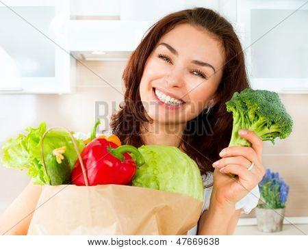 Mulher jovem feliz com legumes numa sacola de compras. Beleza menina na cozinha cozinhar alimentos saudáveis.